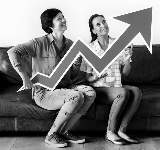 Frauen, die das statistikikonenbrett sitzt auf couch halten
