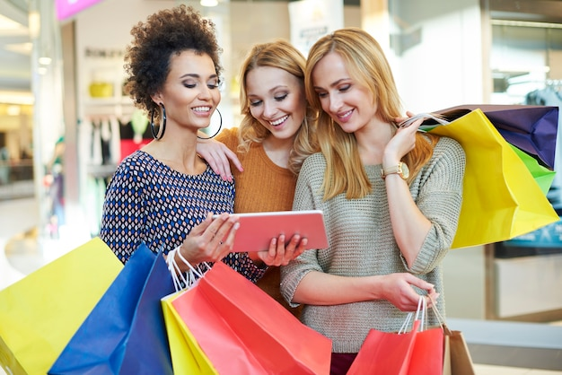Frauen, die das tablet nach dem einkaufen durchsuchen