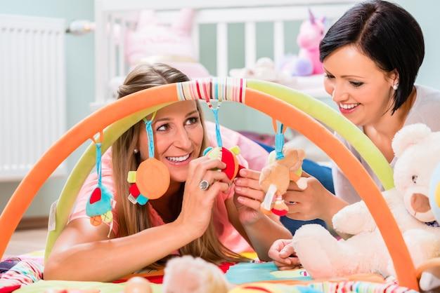 Frauen, die den babyraum vorbereiten, der spielbar für säuglinge vorbereitet