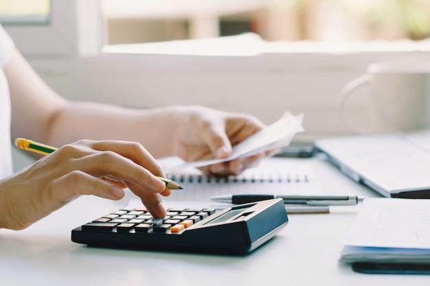Frauen, die den taschenrechner verwenden, um inländische rechnungen zu hause zu berechnen. papierkram erledigen, um steuern zu zahlen