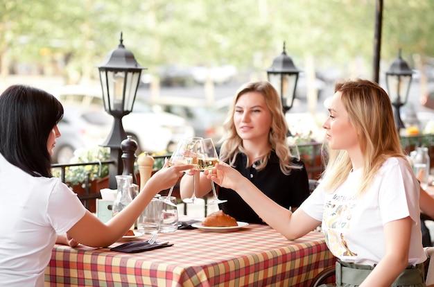 Frauen, die die gläser weißwein halten und einen toast machen. frau jubelt.