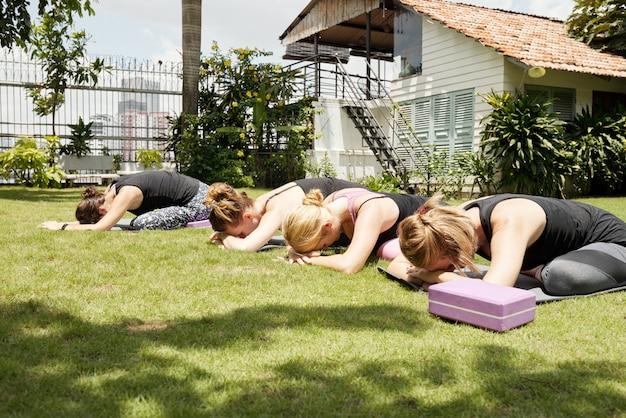 Frauen, die draußen auf grünes gras mit ihren köpfen stillstehen auf händen in einer kinderhaltung ausdehnen
