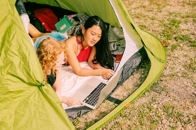 Frauen, die draußen laptop im zelt verwenden