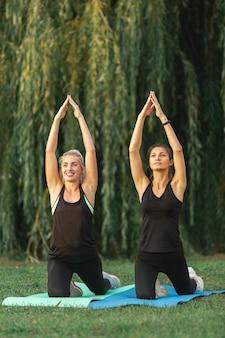 Frauen, die draußen yogaübungen tun