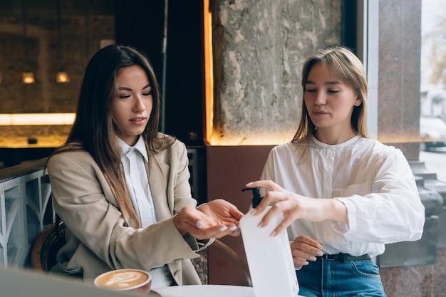 Frauen, die ein antibakterielles antiseptikum verwenden, um im café zu desinfizieren