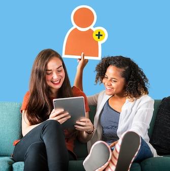 Frauen, die ein freundanforderungssymbol zeigen und eine tablette verwenden