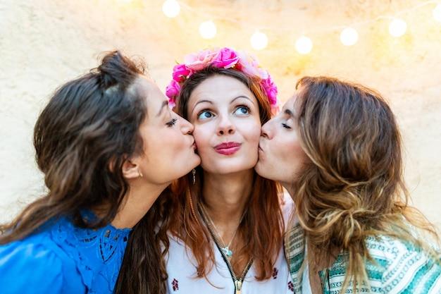 Frauen, die ein glückliches mädchen an ihrem geburtstag küssen