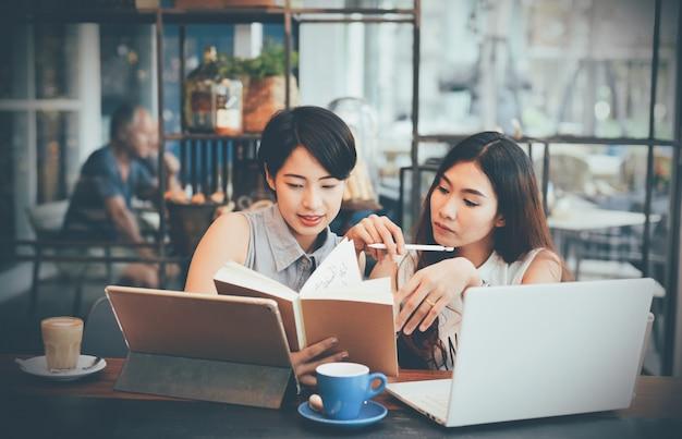 Frauen, die ein notebook in einem coffee-shop überprüfen