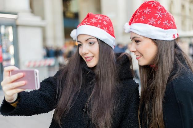 Frauen, die ein selfie beim einkauf in mailand nehmen