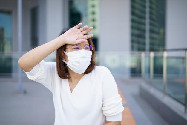 Frauen, die eine gesichtsmaske tragen, schützen den filter vor luftverschmutzung (pm2,5) oder tragen eine n95-maske. schutz vor umweltverschmutzung, anti-smog und viren, luftverschmutzung verursachte gesundheitsprobleme. umweltverschmutzung konzept.