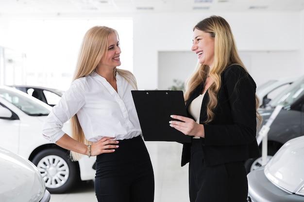 Frauen, die einen deal für ein auto abschließen