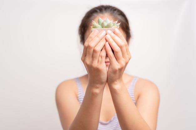 Frauen, die einen grünen kaktusbaum auf weißem hintergrund halten