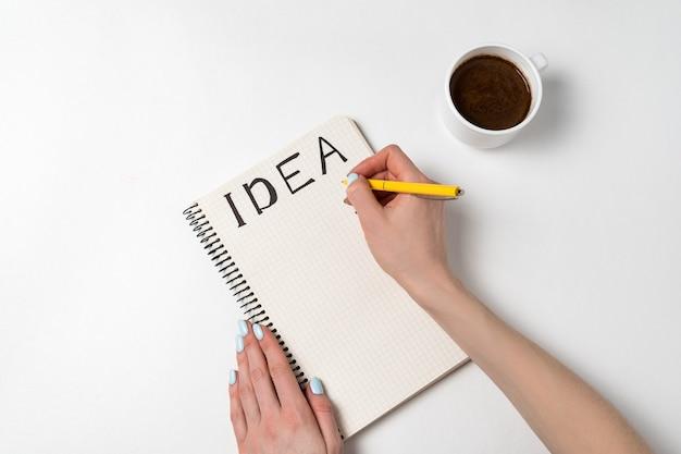 Frauen, die einen stift halten, der in notizbuchidee schreibt. notizblock mit ideen, tasse kaffee auf weißem hintergrund.