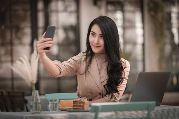 Frauen, die entspannendes selfie sitzen und auf smartphone und laptop auf dem tisch lächeln