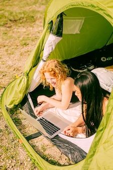 Frauen, die film auf laptop im zelt aufpassen