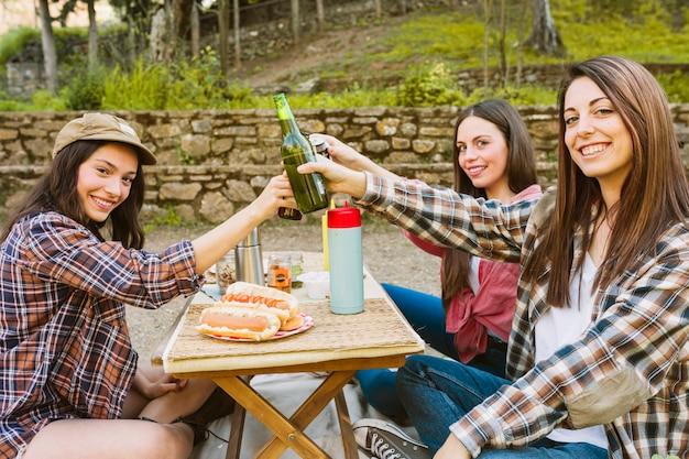 Frauen, die flaschen in der natur klirren
