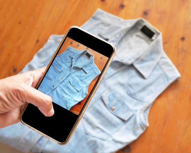 Frauen, die fotohemden mit smartphone-digitalkamera für post nehmen, um online im internet zu verkaufen.