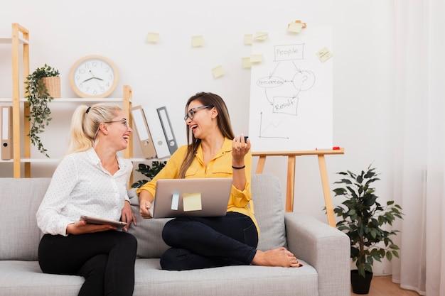 Frauen, die geräte halten und auf sofa sitzen