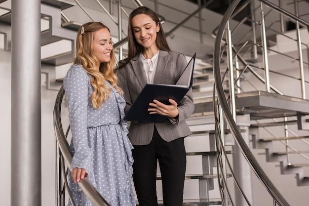 Frauen, die geschäft auf einer treppe sprechen