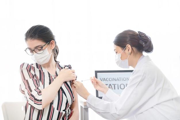 Frauen, die gesichtsmaske gegen covid19-personal und krankenschwestern tragen, die eine spritze verwenden, um impfstoff zu injizieren