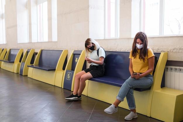 Frauen, die gesichtsmasken tragen, halten abstand