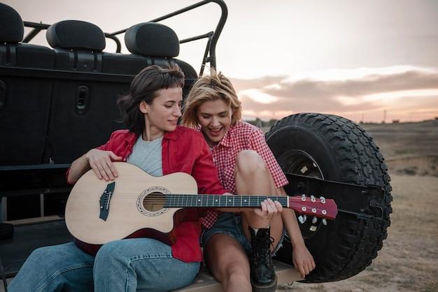 Frauen, die gitarre spielen, während sie mit dem auto reisen