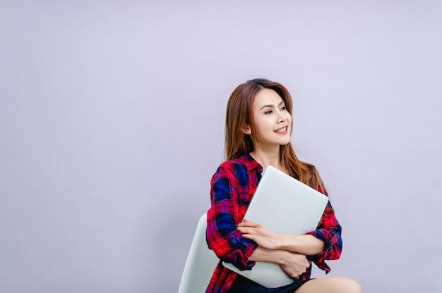 Frauen, die glücklich laptop bei der arbeit sitzen und umfassen