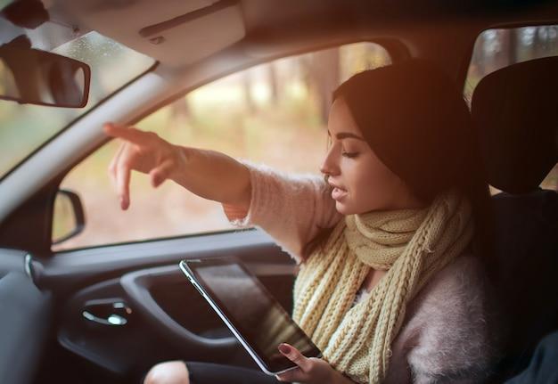 Frauen, die gps auf tablet-computer verwenden, um im auto im urlaub zu navigieren