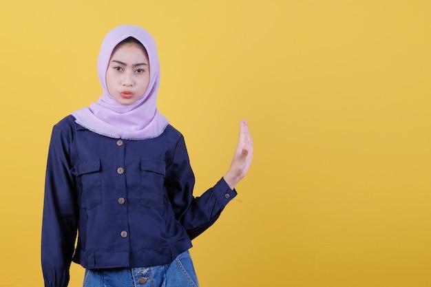 Frauen, die hijabs tragen, machen ernsthaft die handflächen in einer stop-motion und bitten darum, ihr aussehen nicht durch wütendes tragen von freizeitkleidung zu stören, die einschränkung oder ablehnung ausdrückt. komm nicht nah