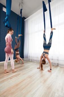 Frauen, die im fitnessstudio anti-schwerkraft-yoga-übungen machen, ein leichter yoga-raum mit großem fenster, eine frau, die mit einem lehrer in einer lufthängematte trainiert.