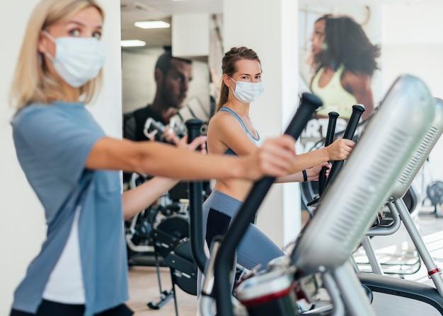Frauen, die im fitnessstudio mit maske trainieren
