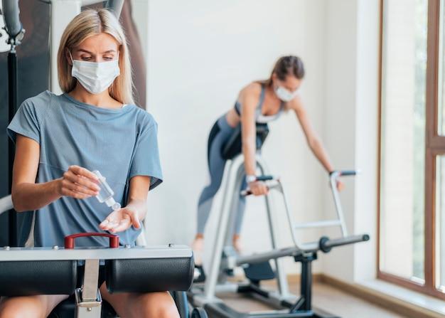 Frauen, die im fitnessstudio mit medizinischer maske trainieren