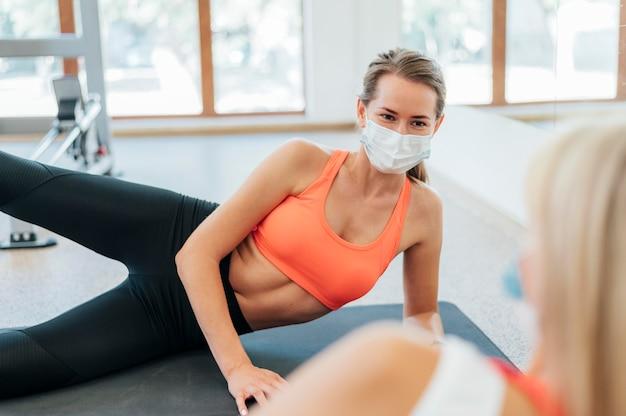 Frauen, die im fitnessstudio zusammen mit der medizinischen maske trainieren