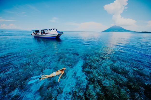 Frauen, die im schönen blauen meer auf der seite des krakatau berges mit einem lehnenden boot schnorcheln