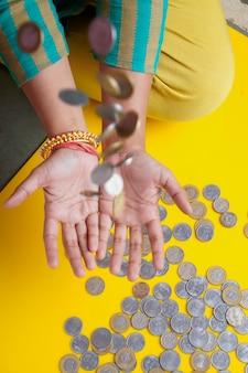 Frauen, die indische rupien-münze in der hand hüpfen