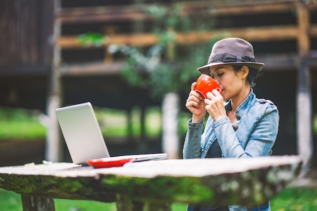 Frauen, die kaffee auf tabelle in der ferienurlaubszeit auf hügelnatur bearbeiten und trinken