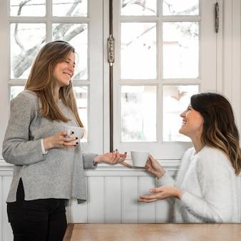 Frauen, die kaffee nahe fenster trinken