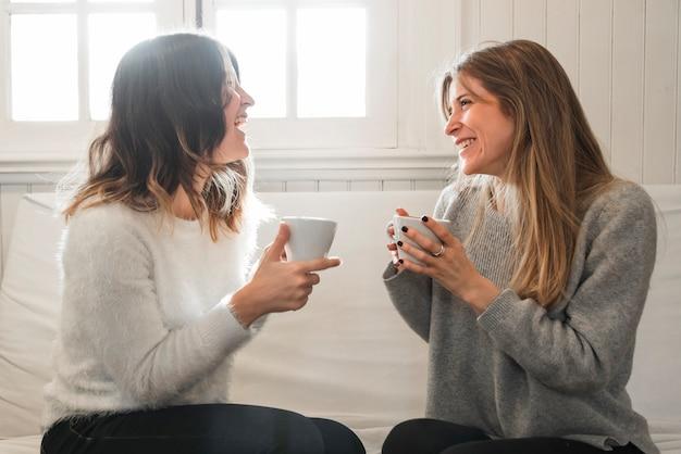 Frauen, die kaffee trinken und auf couch sprechen