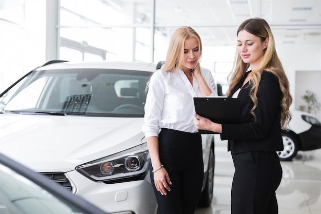 Frauen, die klemmbrett im autohaus betrachten