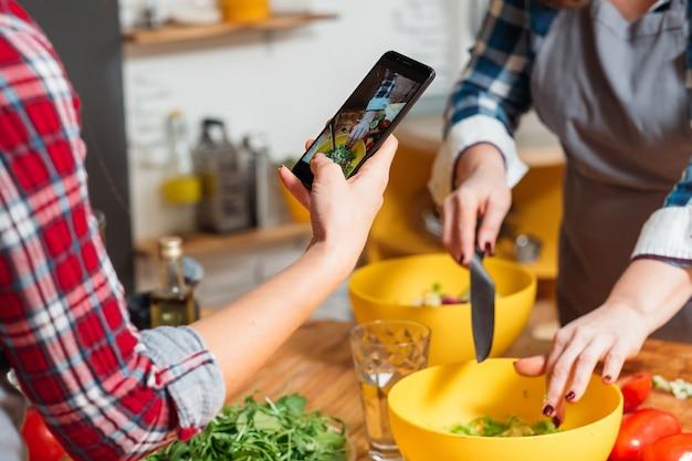 Frauen, die kochprozess auf telefonkamera schießen
