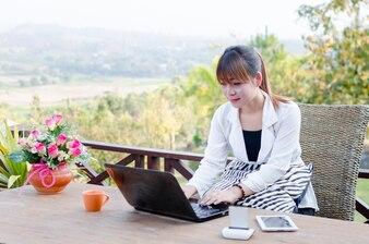 Frauen, die labtop draußen im Garten verwenden