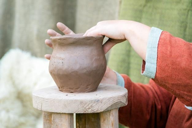 Frauen, die ländliche traditionelle kleidung hand machen keramik tontopf hand.