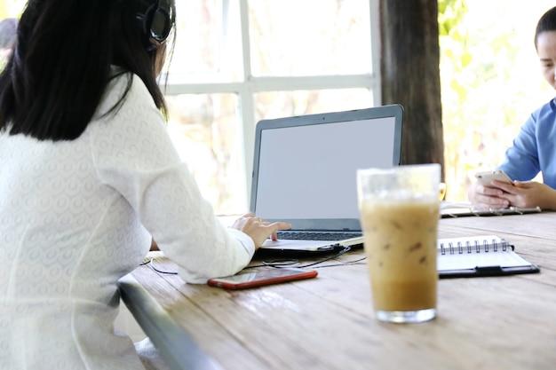 Frauen, die laptopschirm und schreibenslaptop des mannes auf hölzerner tabelle, internet von sachen zeigen