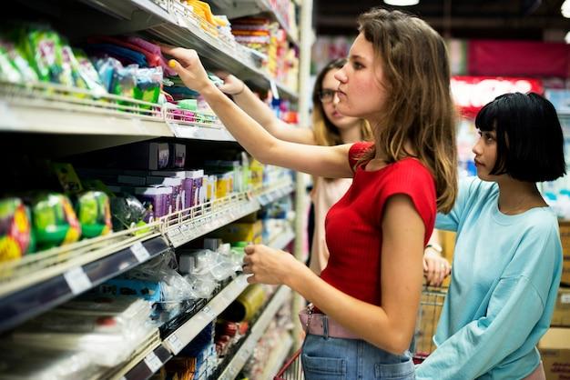 Frauen, die lebensmittel vom supermarkt des supermarktes wählen