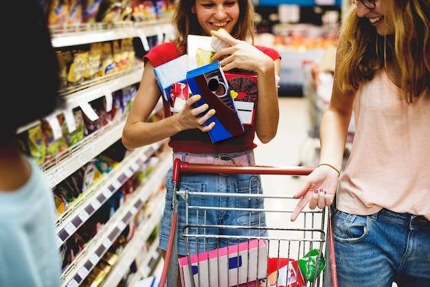 Frauen, die lebensmittel von einem supermarktregal wählen