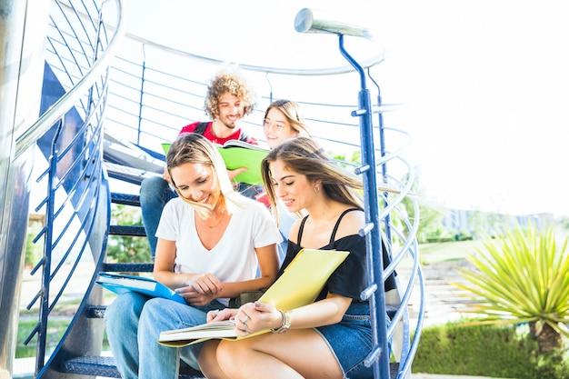 Frauen, die lehrbuch auf treppenhaus nahe freunden lesen