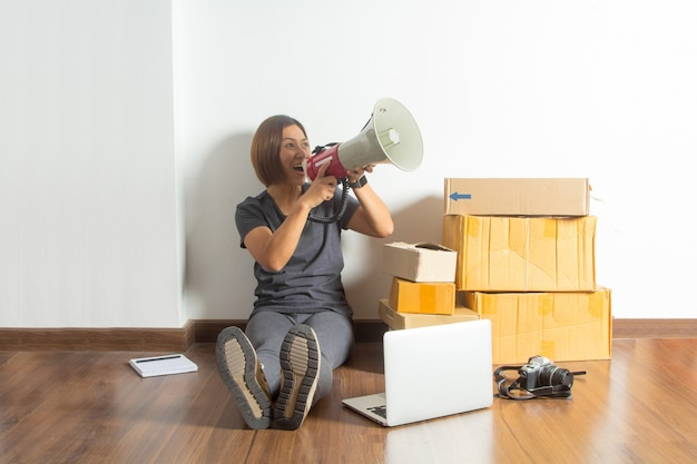 Frauen, die megaphon mit laptop-computer vom haus halten