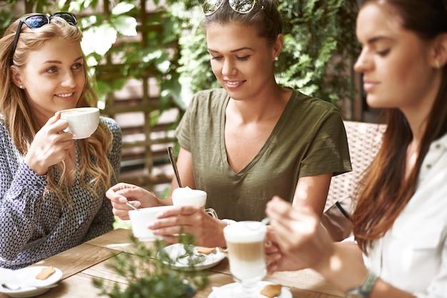 Frauen, die mit freunden einen kaffee trinken