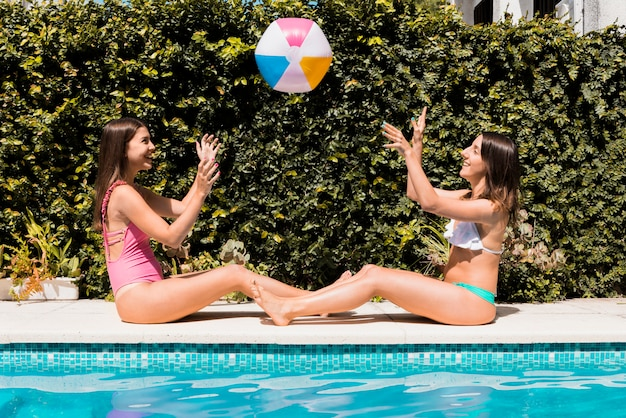 Frauen, die mit gummiball nahe swimmingpool spielen