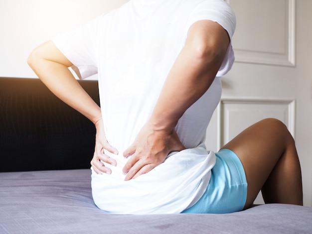 Frauen, die mit rückenschmerzen und taillenschmerzen leiden, sitzen auf bett.